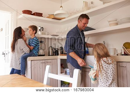 Children Helping Parents In Kitchen With Chores