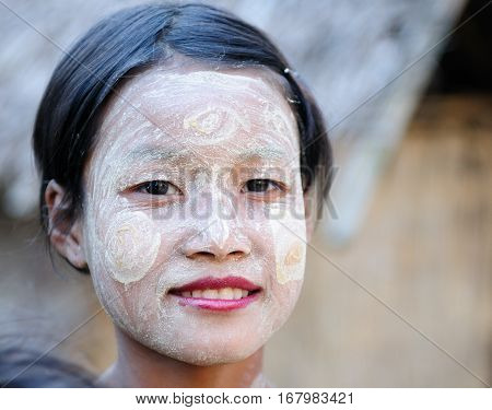 BAGAN MYANMAR - JANUARY 25: Portrait of the Burmese woman in traditional make-up made of Murrays powdered wood in the Bagan town on January 25 2011