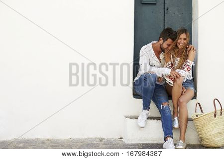 Young adult couple sitting together in doorway, Ibiza, Spain