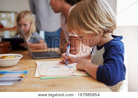 Kids working at kitchen table with their mother, close up