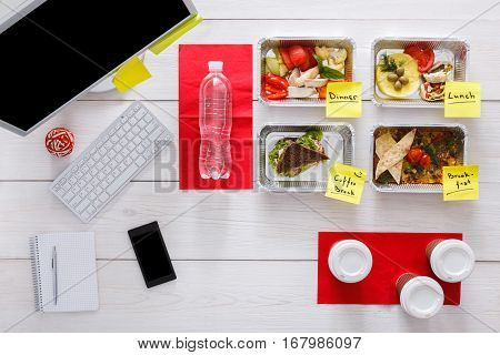 Healthy restaurant food delivery, business lunch and diet plan, fresh daily meals with stickers in office at workplace. Vegetables, meat and fruits in foil boxes. Top view, flat lay on wood