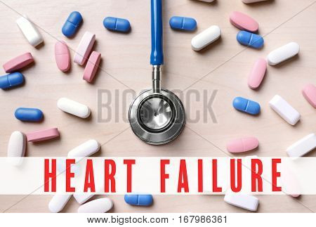 Cardiology and health care concept. Pills and stethoscope on wooden background
