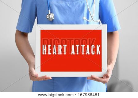 Cardiology and health care concept. Doctor's hands holding board with text HEART ATTACK