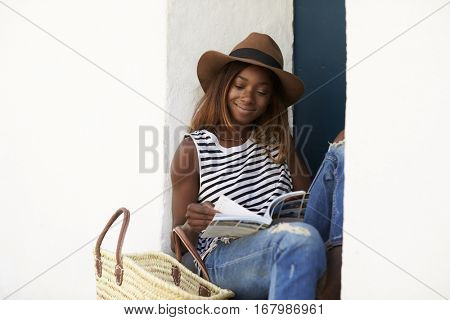 Young woman on sitting on steps reading a guidebook, close up