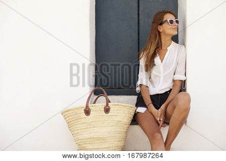Young woman wearing sunglasses sitting on steps looking away