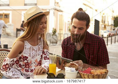 Couple sit reading guidebook outside a cafe, Ibiza, Spain