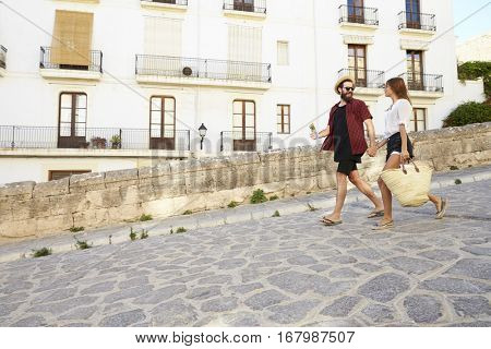 Couple on holiday walking with guidebook, holding hands