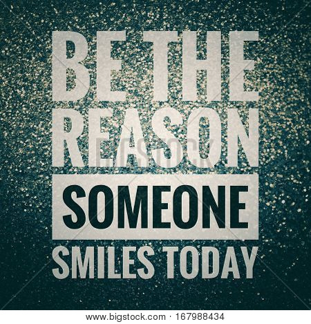 Be the reason someone smiles today inspirational quote on shiny glitter background