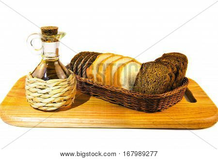Straw braided glass bottle with oil and bread in wicker stay on wooden cutting board isolated on white background