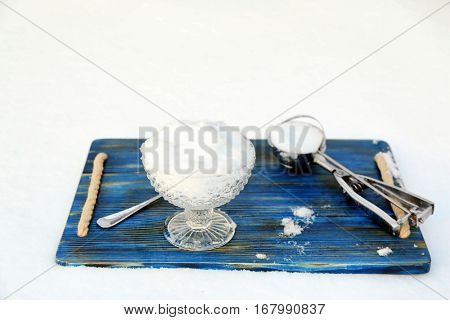 Crystal bowl with snow on blue wooden board outdoors