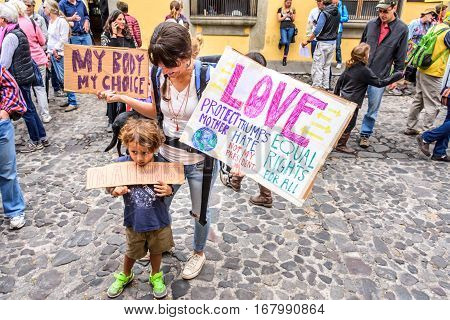 Antigua, Guatemala - January 21 2017: Boy & mother hold signs in peaceful Women's March as part of global protest protecting women's rights & other causes