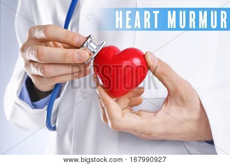 Cardiology and health care concept. Doctor's hands with heart and stethoscope