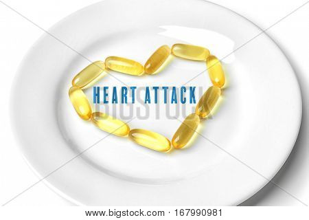 Cardiology and health care concept. Plate with cod liver oil capsules in heart shape on white table
