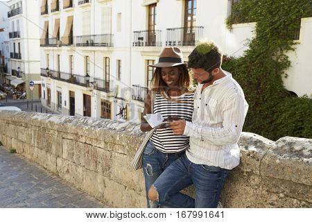 Couple leaning against a wall reading a guidebook, Ibiza