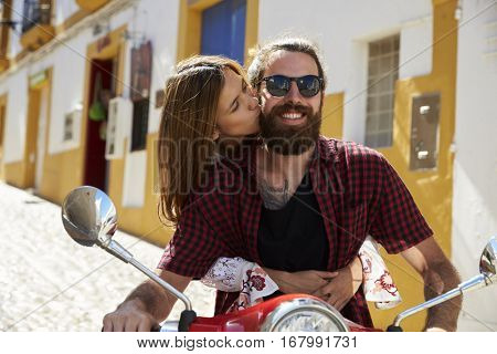 Couple sitting on motor scooter, she kisses him on the cheek