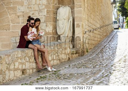 Man embracing his girlfriend on a wall, reading a guidebook