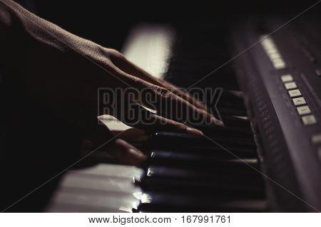 Playing on synthesizer keyboard on black background