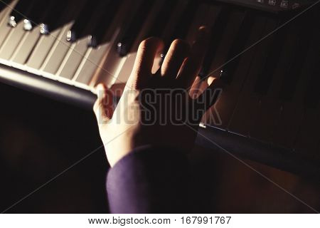 Playing on synthesizer keyboard on performance. Retro effect