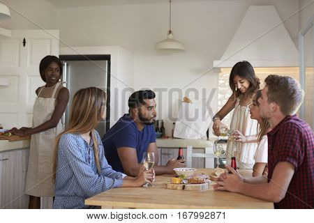 Friends sitting at table, one prepares food, one pours wine