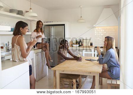 Four women drinking wine in kitchen during a girlsâ?? night in