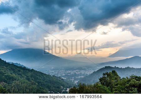 Cloud covered Agua volcano & Fuego volcano at sunset outside Antigua, Guatemala, Central America