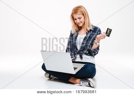 Image of cute young woman using laptop computer isolated on a white background while holding debit card.