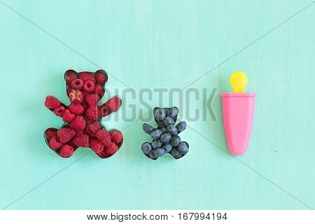 Teddy bear shaped molds for the cookies full of fresh organic raspberries and pink popsicle form for sorbet on turquoise background.