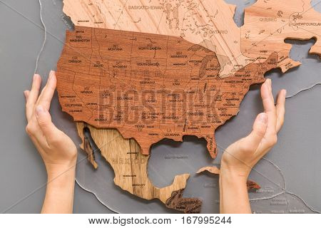 Woman's hands holding handmade wooden map for home decoration. Art and abstract. Different types of wood in shape or continents on light grey background.