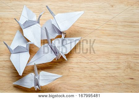 Top View Of Origami Cranes Made From White Paper On A Wooden Table With Copy Space