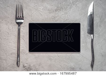 top view of a tablet with blank black screen with fork and knife and lots of copy space for your techno menu text concept