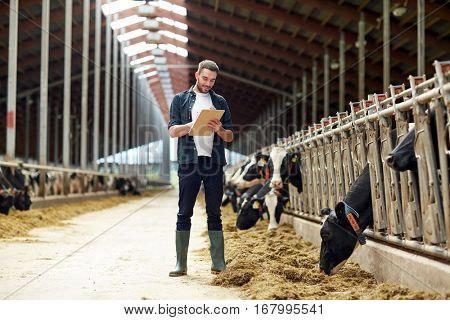 agriculture industry, farming, people and animal husbandry concept - happy smiling young man or farmer with clipboard and cows in cowshed on dairy farm