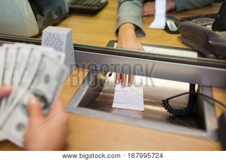 people, withdrawal, saving and finance concept - clerk giving receipt to customer with money at bank office or currency exchanger