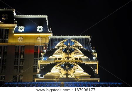 Decorative architecture lit up at night on the exterior of the parisian hotel in the city of macao china.
