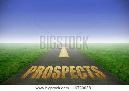 Prospects printed in gold on road with green grass on each side