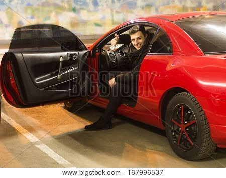 young driver sitting in sport car showing thumbs up with opened door