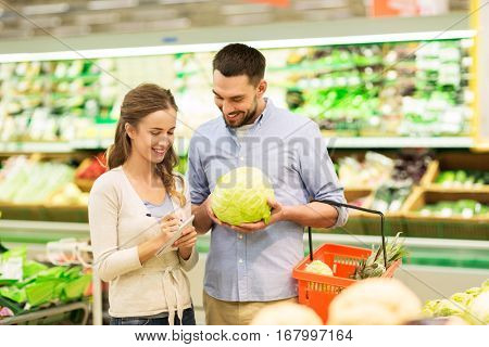 shopping, food, sale, consumerism and people concept - happy young couple with basket and notebook buying cabbage at grocery store or supermarket