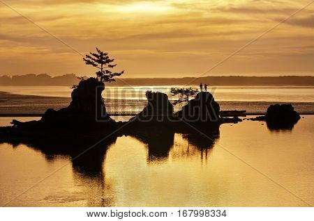 Sunset of ocean beach in Siletz Bay, Oregon with silhouettes of rock and hikers with golden colors