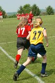 Youth girls on soccer field chasing the ball. poster