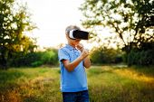 Fascinated little boy using VR virtual reality goggles. outdoor poster