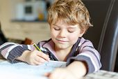 Portrait of cute happy school kid boy at home making homework. Little child writing with colorful pencils, indoors. Elementary school and education. Kid learning writing letters and numbers. poster