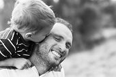 Child playing with his father. Child kissing father. Daddy playing active games with his son outside. Happy family portrait. Laughing dad with little boy enjoying together. Black and white photo. poster
