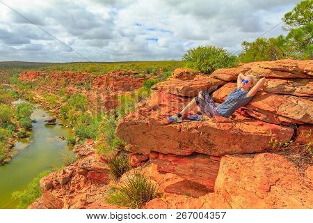 Blonde Woman Resting After Climbing On Red Sandstone Rock At Hawks Head Lookout Over Murchison River