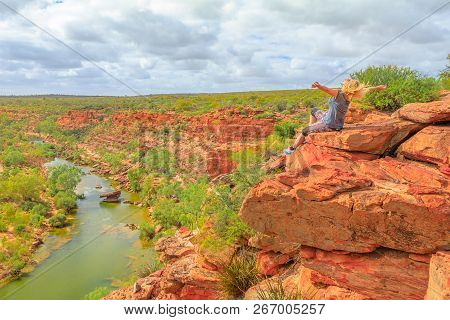 Happy Blonde Woman With Open Arms On Red Sandstone Rock At Hawks Head Lookout Over Murchison River I