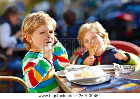 Two Adorable Kids Boys Eating Ice Cream In Outdoor Cafe. Happy Family On Sunny Day. Healthy Children