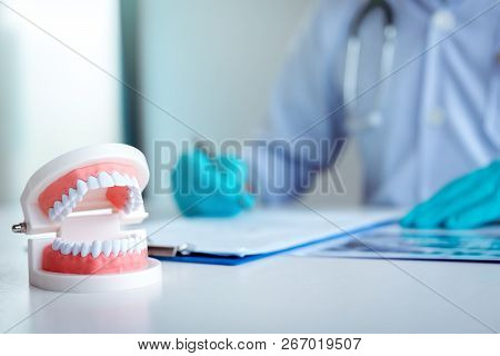 The Dentist Is Writing A Summary Report In His Lab.