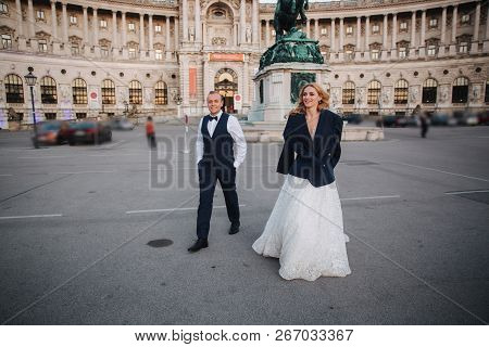 Groom Gives Jaket To His Bride. They Walk Into The City