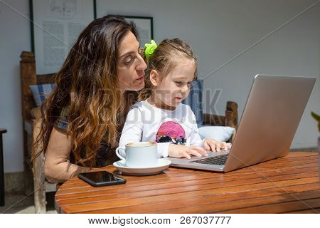 Girl And Mother Watching Notebook Computer