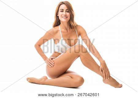 Portrait Of Mid Adult Woman Showing Off Her Fit Long Legs In Studio