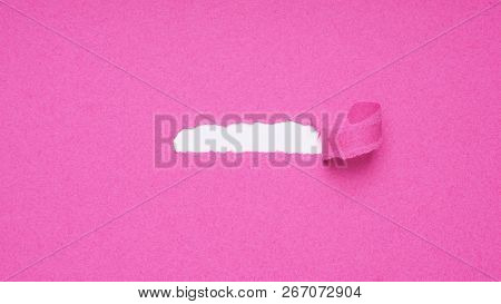 tearing off paper shred to reveal hidden copy space underneath - pink banner background poster