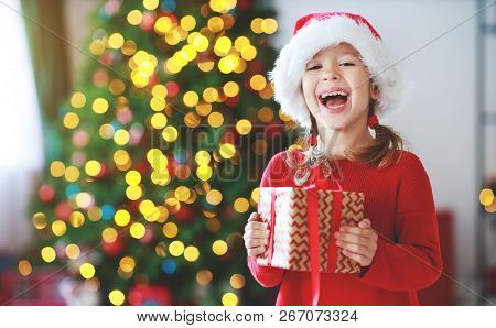 Happy Child Girl With Christmas Gifts Near Christmas Tree In Morning